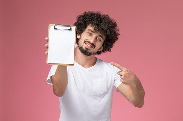 Vooraanzicht jonge man wijst op zijn kantoor notebook