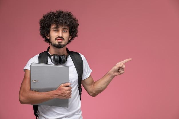Vooraanzicht jonge man wijst op zijn linker richting met bindmiddel en hoofdtelefoon