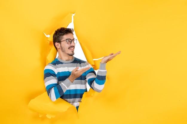 Vooraanzicht jonge man wijzend naar links glurend door gat in papieren gele muur