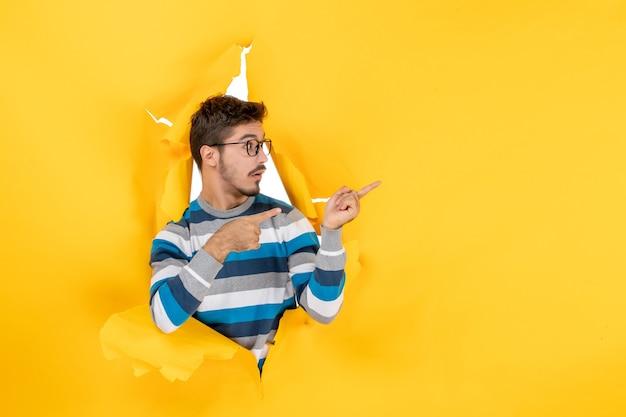 Vooraanzicht jonge man wijzend naar rechts gluren door gat in papier gele muur