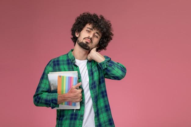Vooraanzicht jonge man zijn nek strekken met notebooks