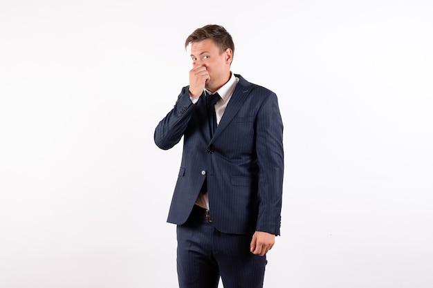 Vooraanzicht jonge man zijn neus sluiten als gevolg van slechte geur in klassieke strikte pak op witte achtergrond emoties menselijke mannelijke pak mannequin
