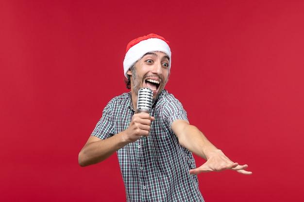 Vooraanzicht jonge man zingen met microfoon op rode achtergrond
