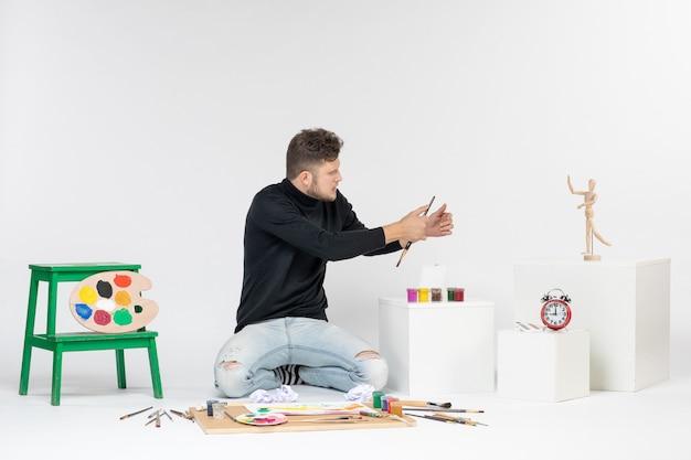 Vooraanzicht jonge man zit rond veel verven en kwasten voor het tekenen op witte muurverf kleur schilderij foto kunstenaar kunst tekenen man