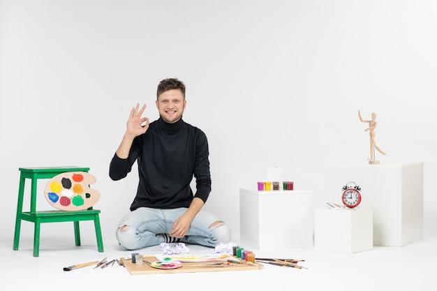 Vooraanzicht jonge man zit rond verf en kwasten om op de witte muur te tekenen kleurenfoto verf kunst schilderij kunstenaar tekenen