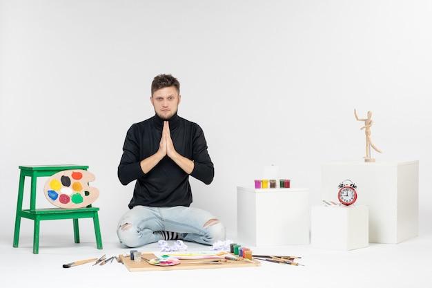 Vooraanzicht jonge man zit rond verf en kwasten voor het tekenen op een witte muur kleurenfoto schilderij kunstenaars verf tekenen kunst