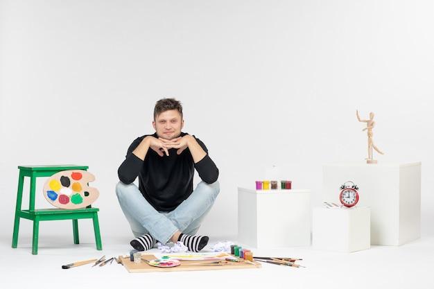 Vooraanzicht jonge man zit rond verf en kwasten voor het tekenen op een witte muur tekenen kleurenfoto's kunstenaar verf kunst schilderij