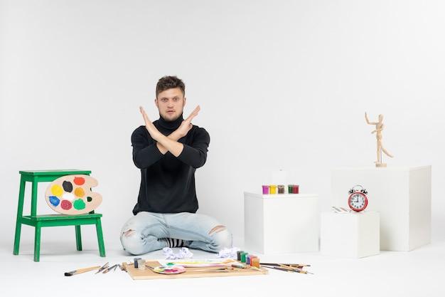 Vooraanzicht jonge man zit rond verf en kwasten voor het tekenen op een witte muur tekenen kleurenfoto schilderen kunstenaars schilderen kunst