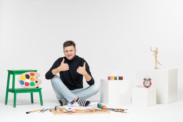 Vooraanzicht jonge man zit rond verf en kwasten voor het tekenen op witte muur kunst tekenen kleurenfoto kunstenaar verf schilderij