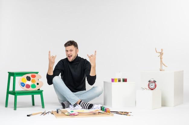 Vooraanzicht jonge man zit rond verf en kwasten voor het tekenen op witte muur kunst tekenen kleurenfoto kunstenaars schilderen schilderen