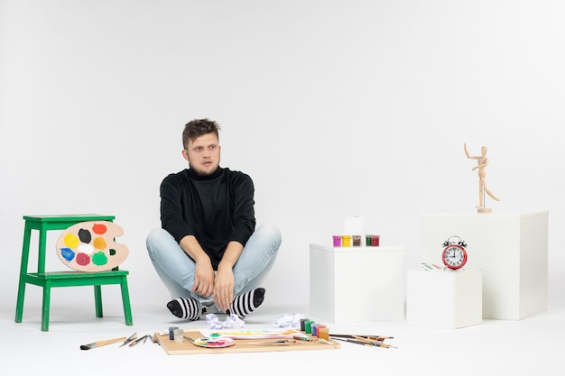 Vooraanzicht jonge man zit rond verven en kwasten om op een witte muur te tekenen kleurenfoto kunstenaar verf kunst schilderijen