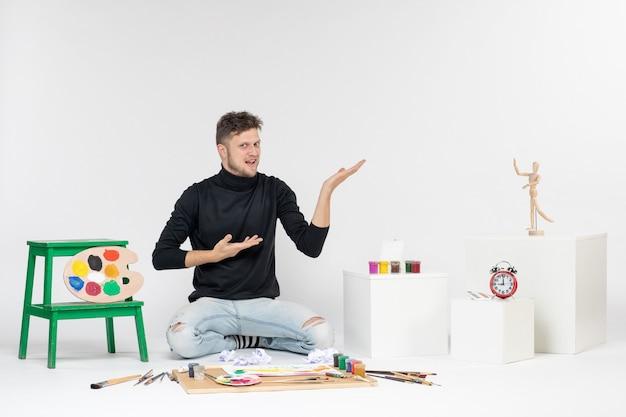 Vooraanzicht jonge man zit rond verven en kwasten om te tekenen op de witte muur kunst teken verf schilderij kleur kunstenaar