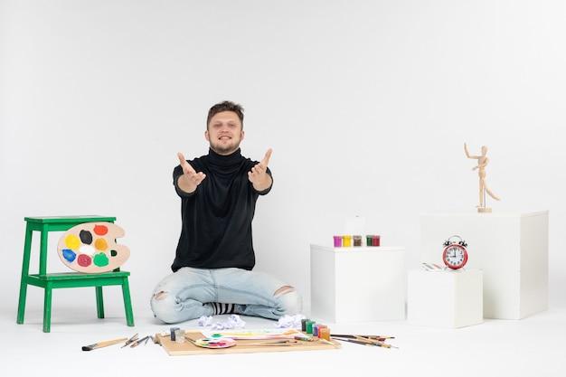 Vooraanzicht jonge man zit rond verven en kwasten voor het tekenen op witte muurverf kunst kunstenaars tekenen kleur schilderij