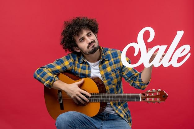 Vooraanzicht jonge man zittend met gitaar op rode muur muziek concert applaus live muzikant kleuren verkoop
