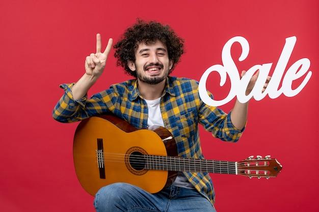 Vooraanzicht jonge man zittend met gitaar op rode muur muziek verkoop speel concert applaus live muzikant kleuren