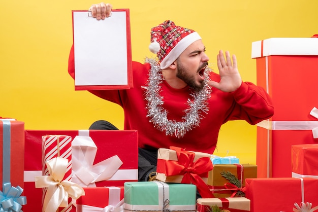 Vooraanzicht jonge man zittend rond kerstcadeautjes met opmerking over geel