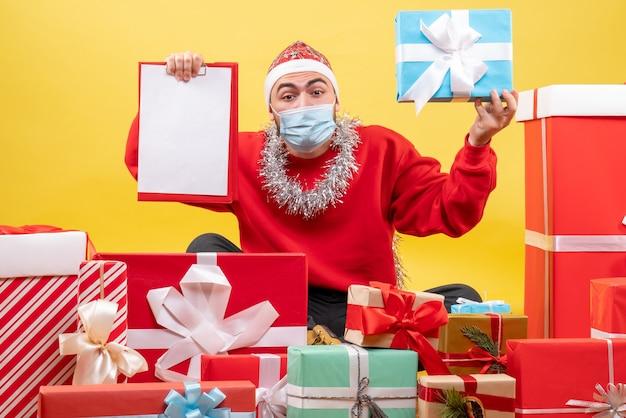 Vooraanzicht jonge man zittend rond kerstcadeautjes met opmerking over gele achtergrond