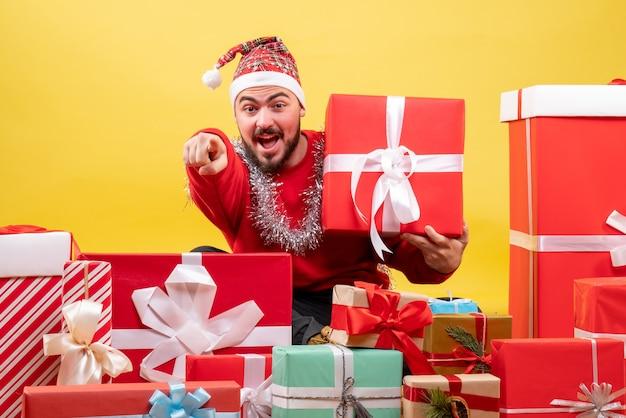 Vooraanzicht jonge man zittend rond kerstcadeautjes op gele achtergrond
