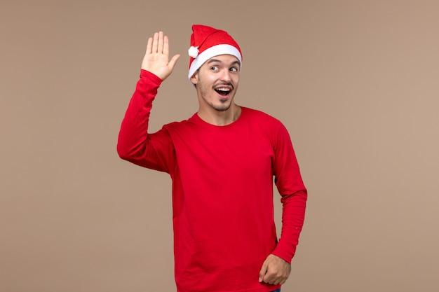 Vooraanzicht jonge man zwaaien en begroeten op bruine achtergrond kerst emotie vakantie man