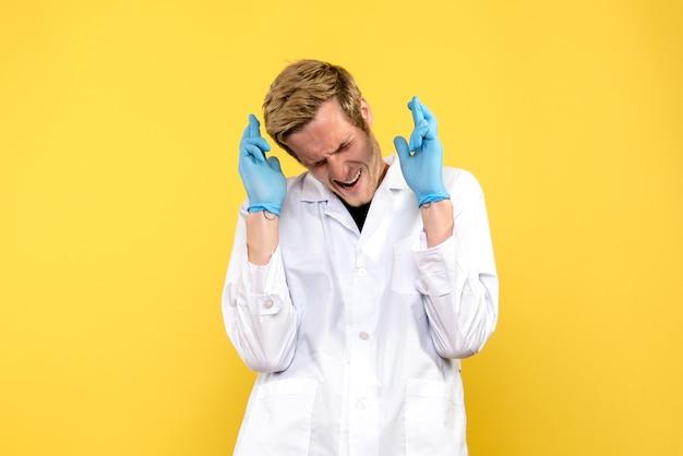 Vooraanzicht jonge mannelijke arts die vingers op gele achtergrond kruist menselijke covid-pandemische dokter
