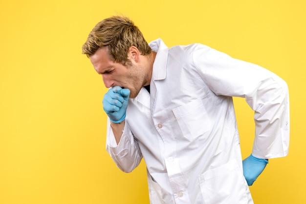 Vooraanzicht jonge mannelijke arts hoesten op gele achtergrond menselijke covid-pandemische medic