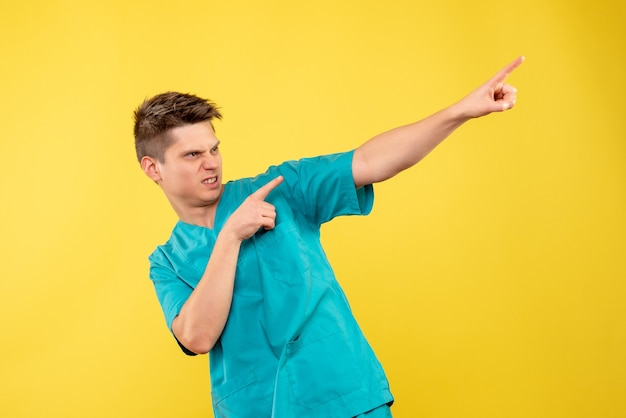 Vooraanzicht jonge mannelijke arts in medisch kostuum op de gele achtergrond