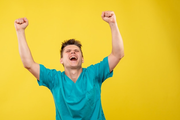 Vooraanzicht jonge mannelijke arts in medisch kostuum op geel