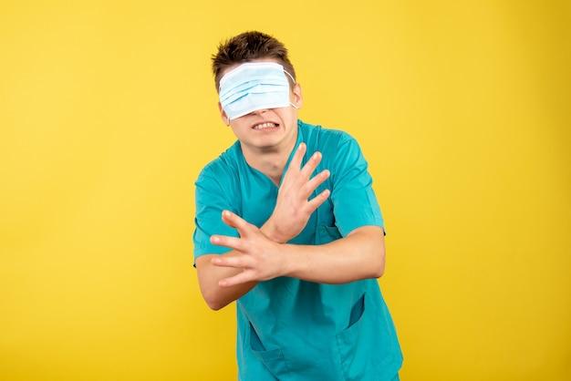 Vooraanzicht jonge mannelijke arts in medisch pak met masker op zijn ogen op gele achtergrond