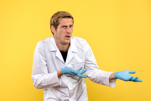 Vooraanzicht jonge mannelijke arts op gele achtergrond menselijke covid pandemie