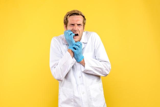 Vooraanzicht jonge mannelijke arts zenuwachtig op gele achtergrond menselijke covid-pandemische medic