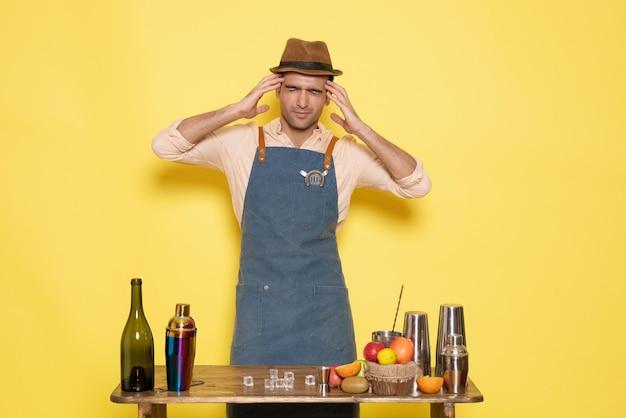 Vooraanzicht jonge mannelijke barman voor tafel met shakers drankjes op gele achtergrond