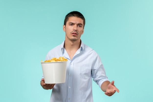 Vooraanzicht jonge mannelijke bedrijf mand met chips op blauwe ondergrond