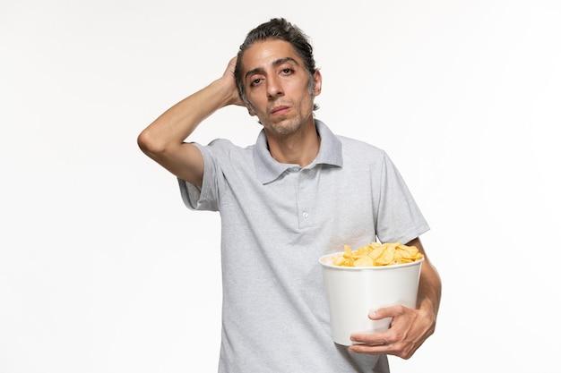 Vooraanzicht jonge mannelijke bedrijf mand met chips op lichte witte ondergrond