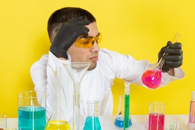 Vooraanzicht jonge mannelijke chemicus in wit pak voor tafel met gekleurde oplossingen houden kolf op het gele bureau wetenschap werk lab