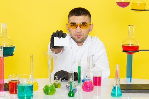 Vooraanzicht jonge mannelijke chemicus in wit pak voor tafel met gekleurde oplossingen met witte kaart op gele muur wetenschap werk lab chemie