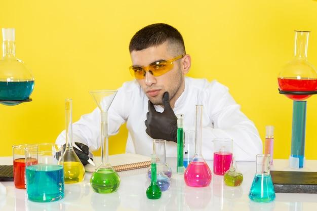 Vooraanzicht jonge mannelijke chemicus in wit pak voor tafel met gekleurde oplossingen notities op lichte muur wetenschap werk lab chemie opschrijven
