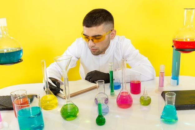 Vooraanzicht jonge mannelijke chemicus in wit pak voor tafel met gekleurde oplossingen notities opschrijven op de gele muur wetenschappelijk werk chemielaboratorium