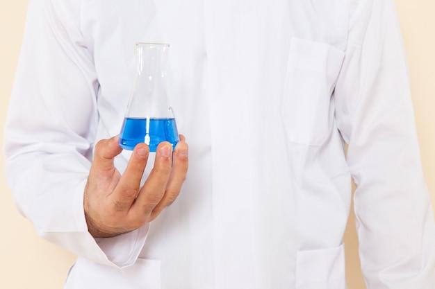 Vooraanzicht jonge mannelijke chemicus in wit speciaal pak met kleine kolf met blauwe oplossing op crème bureau wetenschappelijk experiment chemie wetenschappelijk