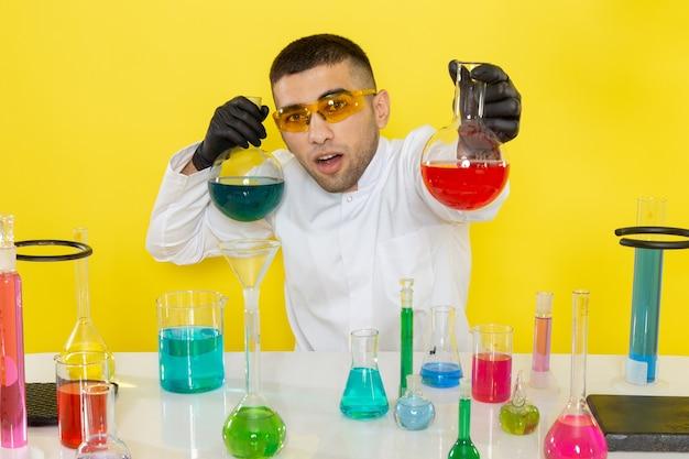 Vooraanzicht jonge mannelijke chemicus in wit speciaal pak voor tafel met gekleurde oplossingen houden kolven op geel bureau wetenschap werk chemisch laboratorium