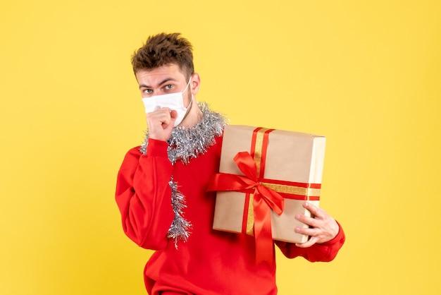 Vooraanzicht jonge mannelijke kerst aanwezig in steriel masker hoesten