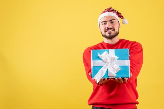 Vooraanzicht jonge mannelijke kerst aanwezig op gele achtergrond