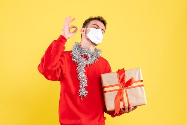 Vooraanzicht jonge mannelijke kerstcadeau in steriel masker