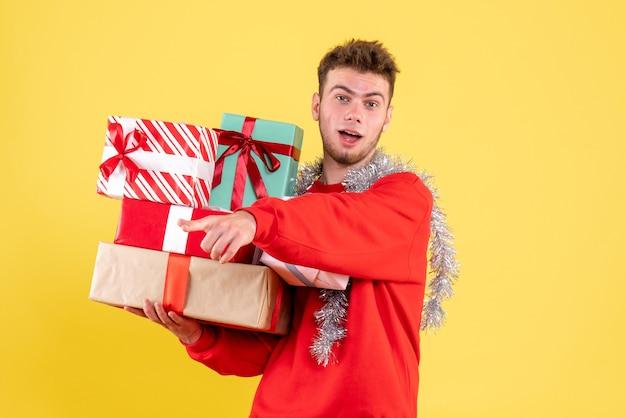 Vooraanzicht jonge mannelijke kerstcadeautjes houden