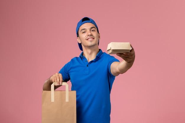 Vooraanzicht jonge mannelijke koerier in blauw uniform en cape met leveringspakketten op zijn handen op de roze muur