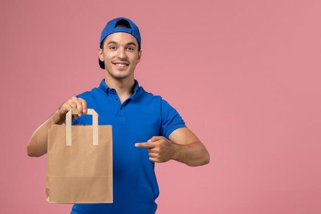 Vooraanzicht jonge mannelijke koerier in blauw uniform en cape met papieren afleverpakket op zijn handen op roze muur