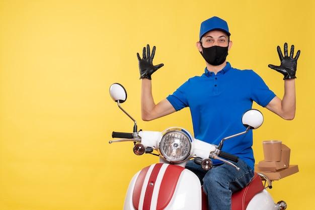 Vooraanzicht jonge mannelijke koerier in blauw uniform en masker op gele achtergrond