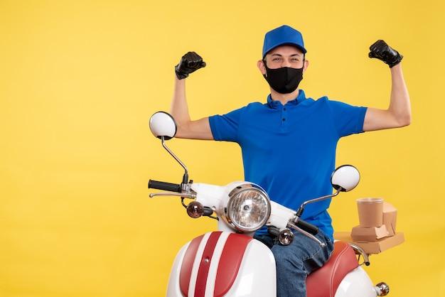 Vooraanzicht jonge mannelijke koerier in blauw uniform op gele achtergrond covid-job pandemie bezorgservice fiets werk