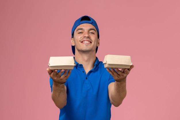 Vooraanzicht jonge mannelijke koerier in blauwe uniforme cape die kleine voedselpakketjes op de roze muur houdt
