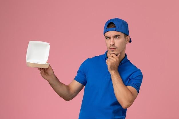 Vooraanzicht jonge mannelijke koerier in blauwe uniforme cape die weinig leeg pakket van het leveringsvoedsel houdt dat aan de roze muur denkt