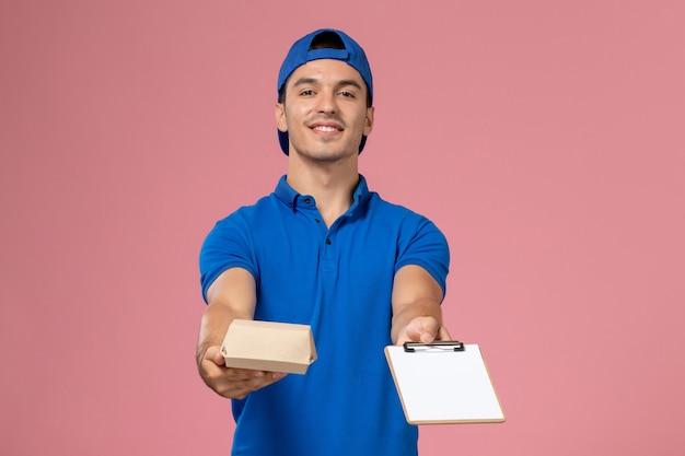 Vooraanzicht jonge mannelijke koerier in blauwe uniforme cape die weinig voedselpakket en blocnote op de lichtroze muur houdt